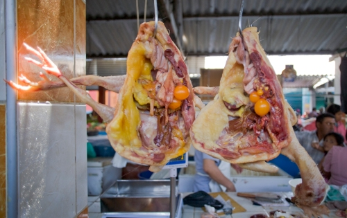 Two chickens severed in half hang by stainless steel hooks in the Chiclayo market.