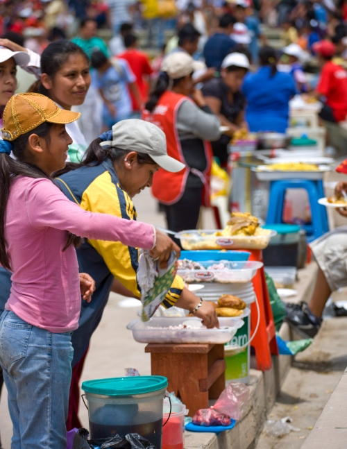A line of people selling food and sodas at a Chiclayo Juan Aurich Futbol game.