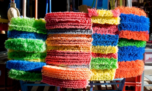Multi colored brooms bristle in the afternoon light.
