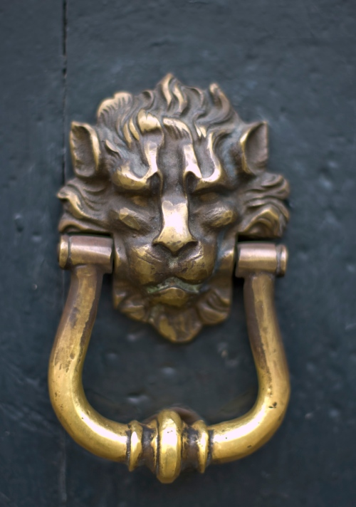 Lion's head knocker on a door in Colonial Trujillo, Peru.