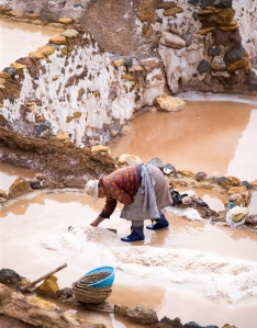 A woman works her salt pool at Salineras